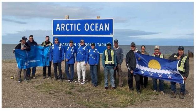 Tłı̨chǫ monitors and Imaryuk and Munaqaiyit monitors posing at the shores of the Arctic Ocean